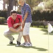 Foto Stock: Father Teaching Son To Play Golf On Putting On Green