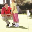 Father Teaching Daughter To Play Golf On Putting On Green — Stockfoto