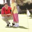padre enseñando a hija a jugar al golf en poner en verde — Foto de Stock
