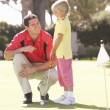 Foto de Stock  : Father Teaching Daughter To Play Golf On Putting On Green