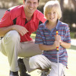 Father Teaching Son To Play Golf On Putting On Green — Stockfoto #4843050