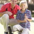 Father Teaching Son To Play Golf On Putting On Green - Photo
