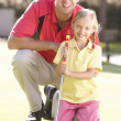 Father Teaching Daughter To Play Golf On Putting On Green - Photo