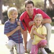 Stock Photo: Father Teaching Children To Play Golf On Putting On Green