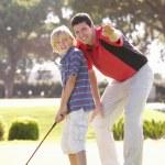 padre enseñando a hijo a jugar al golf en poner en verde — Foto de Stock