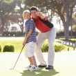 Foto de Stock  : Father Teaching Son To Play Golf On Putting On Green