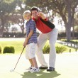 图库照片: Father Teaching Son To Play Golf On Putting On Green