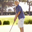 Young Boy Practising Golf On Putting On Green - Stock Photo