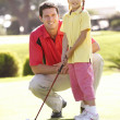 Father Teaching Daughter To Play Golf On Putting On Green — Stock fotografie
