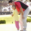 Father Teaching Daughter To Play Golf On Putting On Green — Stock Photo #4843064