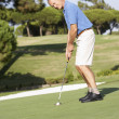 Senior golfeur masculin sur mettre sur green de golf — Photo
