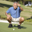 Foto de Stock  : Senior Male Golfer On Golf Course Lining Up Putt On Green