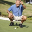 Foto Stock: Senior Male Golfer On Golf Course Lining Up Putt On Green