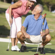 Senior Couple Golfing On Golf Course Lining Up Putt On Green — Foto Stock