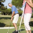 Senior Couple Golfing On Golf Course Lining Up Putt On Green - 