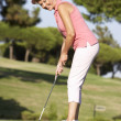 Senior Female Golfer On Golf Course Lining Up Putt On Green - Stock Photo