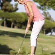 Stock Photo: Senior Female Golfer On Golf Course Lining Up Putt On Green