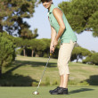 Female Golfer On Golf Course Putting On Green - Стоковая фотография