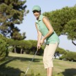 Female Golfer On Golf Course Putting On Green - Stock Photo