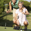 Two Female Golfers On Golf Course Lining Up Putt On Green — Stock Photo #4843098