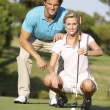 Couple Golfing On Golf Course Lining Up Putt On Green - 图库照片