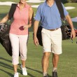 Senior Couple Walking Along Golf Course Carrying Bags — Stock Photo #4843108