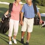 Äldre par promenader längs golfbanan bära väskor — Stockfoto
