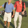 Two Men Walking Along Golf Course Carrying Bags — Stock Photo