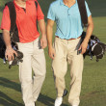 Two Men Walking Along Golf Course Carrying Bags — Stock Photo #4843114