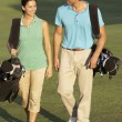Couple Walking Along Golf Course Carrying Bags — Stock Photo #4843116