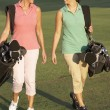 Two Women Walking Along Golf Course Carrying Bags — Stock Photo