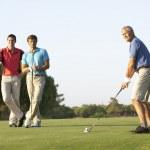 grupp av manliga golfare tee off på golfbana — Stockfoto