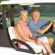 Senior koppel in golf buggy rijden op golfbaan — Stockfoto