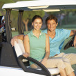 Couple Riding In Golf Buggy On Golf Course — Stockfoto