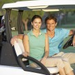 Couple Riding In Golf Buggy On Golf Course — Lizenzfreies Foto