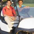 Two Male Golfers Riding In Golf Buggy On Golf Course — Stock Photo
