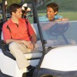 Stock Photo: Two Male Golfers Riding In Golf Buggy On Golf Course