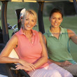 Two Female Golfers Riding In Golf Buggy On Golf Course — Stock Photo
