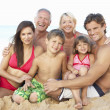 Portrait Of Three Generation Family On Beach Holiday - Stock Photo
