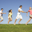 Young couples running through field — Stock Photo