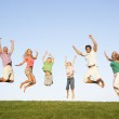 Young couple with grandparents and children jump in a field — Stock Photo