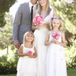 Bride And Groom With Bridesmaid At Wedding - Stock Photo