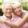 Senior couple relaxing together in park - Stock Photo