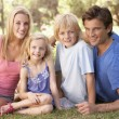 Young parents with children posing in a park - Stock Photo