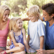 Young parents with children talking in a park - Stock Photo