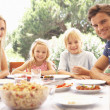 Parents, with children, enjoy a picnic — Stockfoto