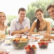 Two young couples eating outdoors - Foto Stock