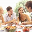 Foto Stock: Two young couples eating outdoors