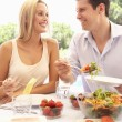Young couple eating outdoors — Stock Photo #4843697