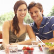 Young couple eating outdoors — Stock Photo #4843703